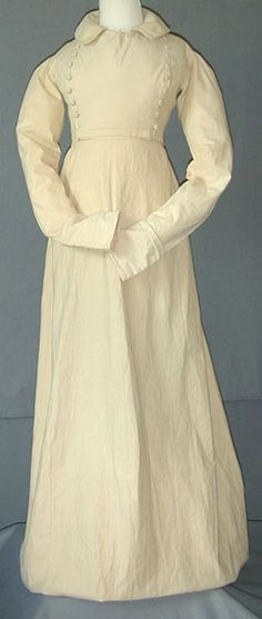Riding habit of cream-color holland (heavy cotton), c. 1810. Probably made for a hot climate. When walking the wearer would tie up the skirt to reduce the length, and then the tapes would be released and the whole of the skirt would be lengthened for riding. The skirt was meant to be long enough to cover the animals knees.