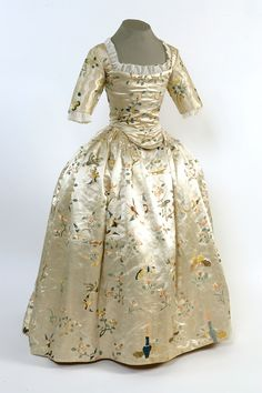 This is an English girl's dress of about 1760. It is a fashionable dress made from expensive Chinese export silk, but it has a thrifty secret.      To us, it often looks as if children in the past were miniature adults, particularly in the way they were dressed. This girl's dress echoes fashionable women's dresses of the period. like them, it was worn over tight stays and voluminous petticoats.