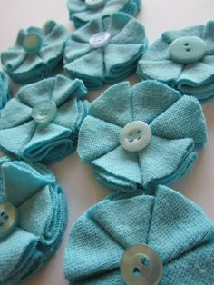 DIY Fabric Flowers... what to do with buttons and fabric and maybe a circle cutter.   I could see this out of fake leather, microsuede, wool felt, polar fleece...
