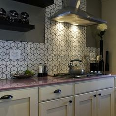 The eye is drawn to your backsplash, making it a great area to step up the quality of materials. Here, a black grout is used to accentuate the modern geometric pattern of these Heath Ceramic tiles.