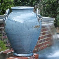 An impressive large urn with two decorative handles. This urn has been glazed in soft blue and antiqued lightly. A nice piece that is equally at home inside or