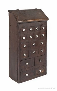 "Pennsylvania walnut apothecary cupboard, early 19th c., with eighteen drawers under a canted lid, 30 1/2"" h., 16"" w., 8"" d."