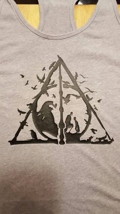 Are you still a Harry Potter fan? Then youll love this awesome design of the Three Brothers and the Deathly Hallows! Its perfect to wear year round, just throw an extra layer on top, and youre ready to go this fall/winter.  NOTE: most shirts are not usually kept in stock at this point in time, so it may take the full turnaround time for me to receive the shirts, make them, and then mail them. But I am happy to order you the size and color of this shirt you want, it just may delay your o...