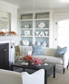 Love the colors in this cottage living room-white paint is Marshmallow Sherwin Wms 7001 & the Moody gray-blue in the bookcase is Tradewind SW 6218