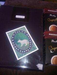 Arvoringistä musta aluslakana, 2 tyynyliinaa sekä 2 pakettia espresso supremo-kapseleita.