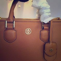 "Tory burch Robinson large pebbled square tote Tory Burch pebbled leather tote with golden hardware. Rolled top handles with hanging covered key ring; 4"" drop. Detachable, adjustable shoulder strap; 17 1/2"" drop. Double-T logo medallion centered at front. Zip compartments frame front and back. Open top with magnetic snap closure. Inside, fabric lining; one zip and two open pockets. 10""H x 15""W x 6 1/2""D; authentic and NWT with dust bag. Tory Burch Bags Totes"