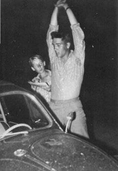 Elvis from his time in Germany - stretching beside what appears to be a young fan seeking an autograph - and a car - maybe a volkswagen.