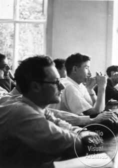 L-R: Amaldi and Delbruck and listen to a lecture in a classroom at the Copenhagen Conference at the Niels Bohr Institute. This photograph was originally image number 20 in an album owned by Victor Weisskopf. Credit line: Photograph by Paul Ehrenfest, Jr., courtesy AIP Emilio Segre Visual Archives, Weisskopf Collection