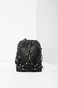 This vegan black leather bag by UNIF has harness detailing with silver studs, zip closures at top, and full lining with zip pockets.
