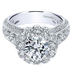 18K White Gold Tapered Channel Diamond Engagement Ring with Floral Halo. This ring features 2.33cttw of round diamonds with a substantial diamond shank of channel set round diamonds accented by bead s