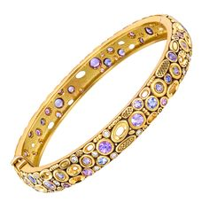 "ALEX SEPKUS .""Oval Windows"" hinged bangle bracelet, set with pink and purple sapphires, accented by round-cut diamonds, the gemstones altogether weighing approximately 3.20 total carats, mounted in intricately hand-engraved and pierced 18k yellow gold, signed Alex Sepkus. Small size (interior dimensions: 54mm x 50mm). 21st Century"