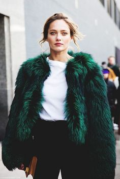 Go for a sophisticated look in a dark green fur jacket and black slacks.  Shop this look for $924:  http://lookastic.com/women/looks/brown-clutch-black-dress-pants-white-crew-neck-t-shirt-dark-green-fur-jacket/5508  — Brown Leather Clutch  — Black Dress Pants  — White Crew-neck T-shirt  — Dark Green Fur Jacket