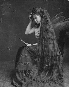 A beautiful young Victorian woman with ankle grazing hair wearing ethereal fairy wings.
