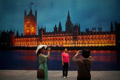 """Tourists take photos near a panoramic photo of the Houses of Parliament in London, exhibited inside China's National Aquatic Center, also known as the """"Water Cube"""", in Beijing, China, June 7, 2012. The """"Water Cube"""" was the 2008 Beijing Olympic venue for swimming, diving, synchronized swimming, and water-polo. (Alexander F. Yuan/Associated Press)"""