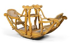 A late Victorian beech and cane child's seesaw, circa 1895  the centre structure also with a seat and a pair of hinged handles  70cm. high., 149cm. wide; 2ft. 3½in., 4ft. 10½in.