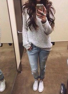 light blue slightly tattered cuffed skinny jeans, light grey oversized sweater, and all white converse tennies.