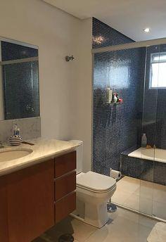 Banheiro com banheira e box, revestido em pastilha de vidro. Bancada de mármore.