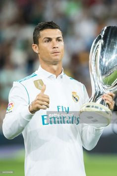 Cristiano Ronaldo #7 of Real Madrid gives a thumbs up as he holds up the UEFA Super Cup trophy prior to the La Liga match between Real Madrid and Valencia C.F. at the Santiago Bernabéu Stadium on August 27, 2017 in Madrid, Spain. The match ended in a tie of 2 to 2.