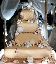 Beach-themed wedding cake with seashells and coral.