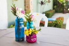 Centro de mesa: flores e garrafas coloridas