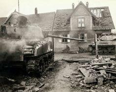 Un passé émouvant de chasseur de chars américain du réservoir qui a été éliminé lors de la bataille chaude quand les américains ont repris la ville. Entre les deux véhicules blindés, deux hommes médicaux sont ramasser un soldat américain qui a été tué dans le combat pour prendre la ville