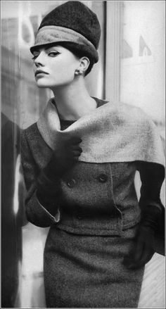Model in slim Oxford-gray wool suit, the jacket and scarf reverses to light gray, by Frank Gallant, double-header hat by Emme, photo by Saul Leiter, Harper's Bazaar, July 1959