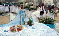 """Brazil Pays Tribute to Iemanja, Goddess of the Sea:  """"Women carry flower offerings for Iemanja on Copacabana beach, Rio de Janeiro, Brazil on December 29, 2012. Tens of thousands of people across Brazil on Saturday paid their annual tribute to Iemanja, the goddess of the sea in the Afro-Brazilian religion Candomble, offering flowers, food and perfume, as drums belted out African rhythms."""""""