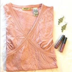 listing Pretty in Pink Tee XL Pretty in Pink V neck t shirt with empire detail. Ultra soft. This is your basic tee dressed up a bit. Meant to look wrinkly! 100% polyester. Stamp 10 Tops Tees - Short Sleeve
