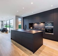 Matte black cabinetry screams luxury in this modern kitchen by Light timber flooring is the perfect contrast against dark finishes. Kitchen Island Storage, Farmhouse Kitchen Island, Modern Kitchen Island, Small Space Kitchen, Kitchen Room Design, Open Plan Kitchen, Modern Kitchen Design, Kitchen Layout, Kitchen Interior