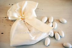 Silk Bomboniere Pouch in white or ivory dressed with satin ribbon and pearl detail and filled with 5 sugar almonds from Pandora designs Melbourne