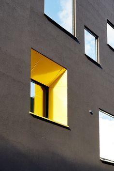 A yellow window on a plain grey wall