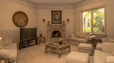 Romantic living room with marble fireplace and beautifully detailed carpet.