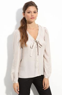 """Slightly sheer blouse with satin trim and ties finishing the V-neckline and gently puffed long sleeves."" Via Nordstrom, $88."