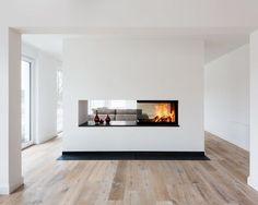 Dreisseitig einsehbarer Kamin als Raumteiler zwischen Kueche und Wohnraum.