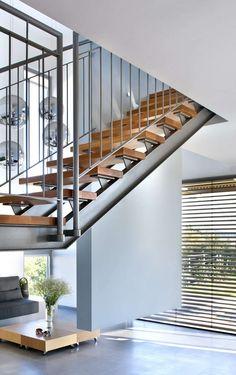 escalier en métal gris à marches de bois sans contremarche avec un garde-corps à barres verticales
