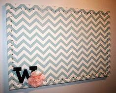 A giant fabric covered cork board... Good idea to add the chevron style to the room..