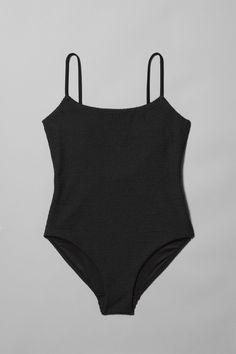 The Sun Swimsuit has a classic cut with a ring neckline and a U-shaped back. Made of structured material, it has thin elasticated straps. Made from recycle