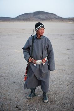 Mongolia's Nomads: A herder holding his gun and wearing his finest leather-and-silver belt stands for a portrait near his ger (yurt) in the Gobi. Historian and anthropologist Jack Weatherford says traditionally only men wore sashes or belts over their deel (robes) and this was a symbol of manhood.