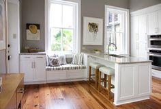 Love the floors, built-in window seat and peninsula with barstools