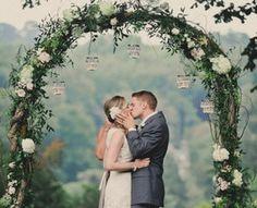 Coppia di sposi sotto un arco floreale