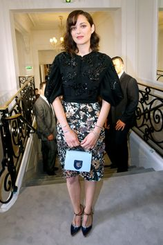 Marion Cotillard wearing a black lace top. a floral pencil skirt, black pumps, and a mini blue Dior bag at the Dior Couture show in Paris.