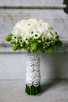 Bridal bouquet made of white ranunculas collared by green arabicum and finished in an eyelet inspired lace. Created by JL DESIGNS