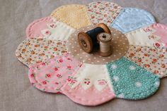hello all! I have a little something to show you. I've sewn up those dresden plates and now I've got a pile of trivets for the table... The first one I sewed I used my EZ dresden plate template, which creates 20 thinner wedges of fabric, and I sewed it...