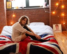 love everything about this room. exposed brick wall. white lights. bedspread. bowie cover.
