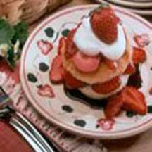 Strawberry Angel Shortcake - Miniature angel food cakes topped with amaretto-laced fudge sauce, sliced strawberries and a dollop of sweetened whipped cream.