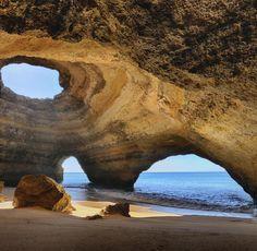 """Praia de Benagil: Weiter östlich, am Strand von Benagil, ist eine riesige Felshöhle der eigentliche Touristenmagnet. Schwimmend oder per Boot erreicht man bei Ebbe den als """"Kathedrale"""" bekannten, vom Meer ausgespülten Hohlraum. Er findet sich auf vielen Postkarten der Algarve wieder."""