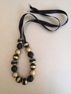 Sixteen small wooden beads hand-painted black and gold. Placed on a black ribbon that can be adjusted to various lengths.
