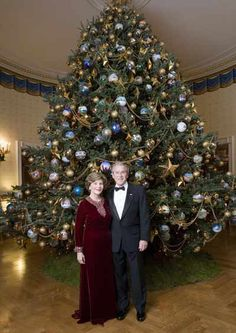 Celebrating the 2007 holiday season, President George W. Bush and Mrs. Laura Bush pose in front of the Christmas Tree in the Blue Room of the White House