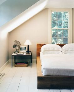 """See the """"The Guest Room"""" in our Home Tour: Country Cottage gallery-- The guest room above the kitchen is fitted out with an oak bed, a side table by Florence Knoll, and a 19th-century rosewood lamp."""