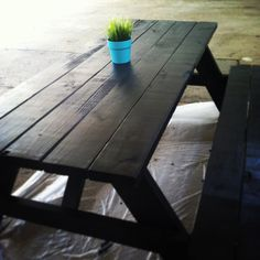Picnic tables painted black with a pop of color.
